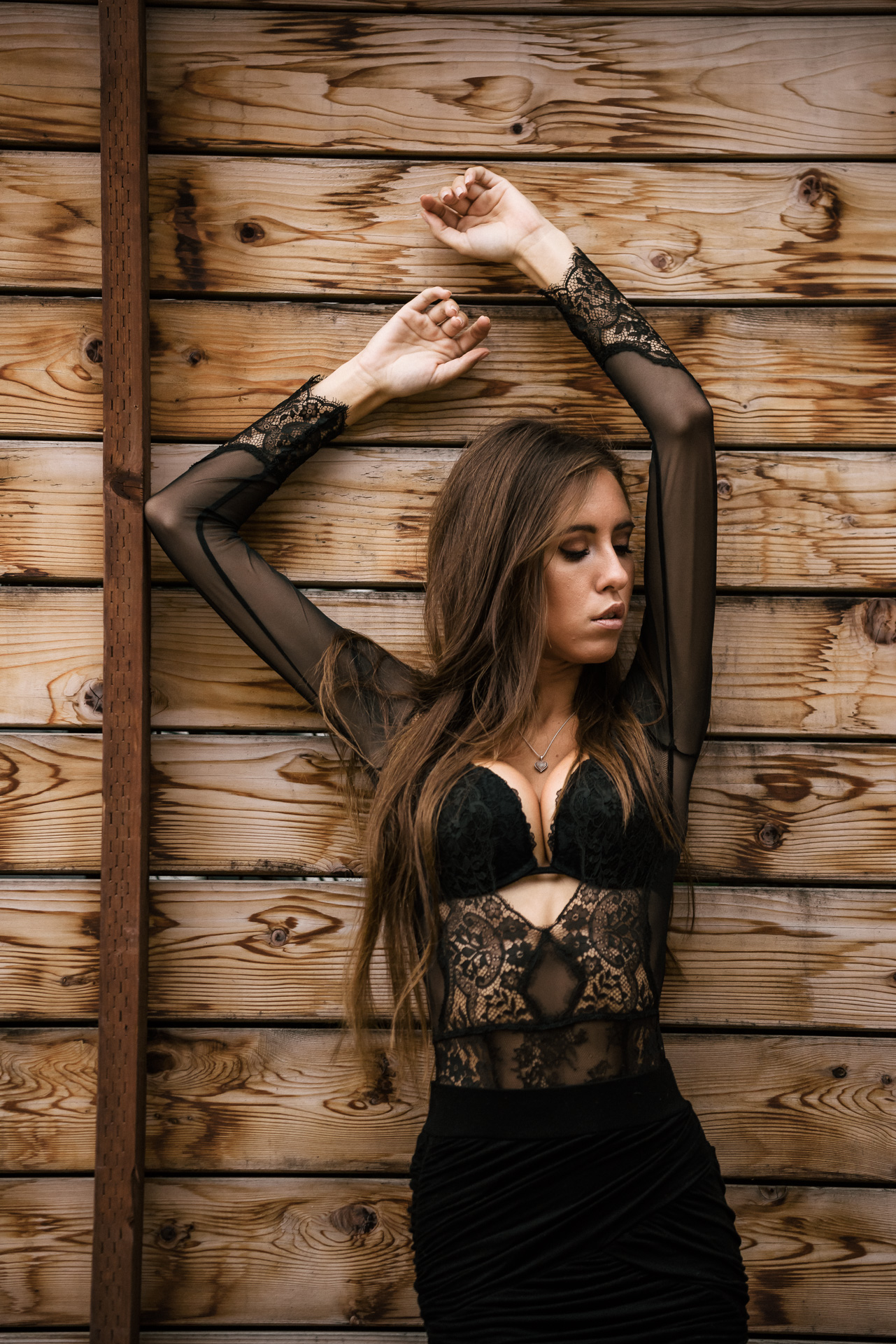 beautiful model in black lace poses against textured wooden wall at The Hungarion Brunette Lingerie as outerwear fashion photoshoot in Venice Beach California