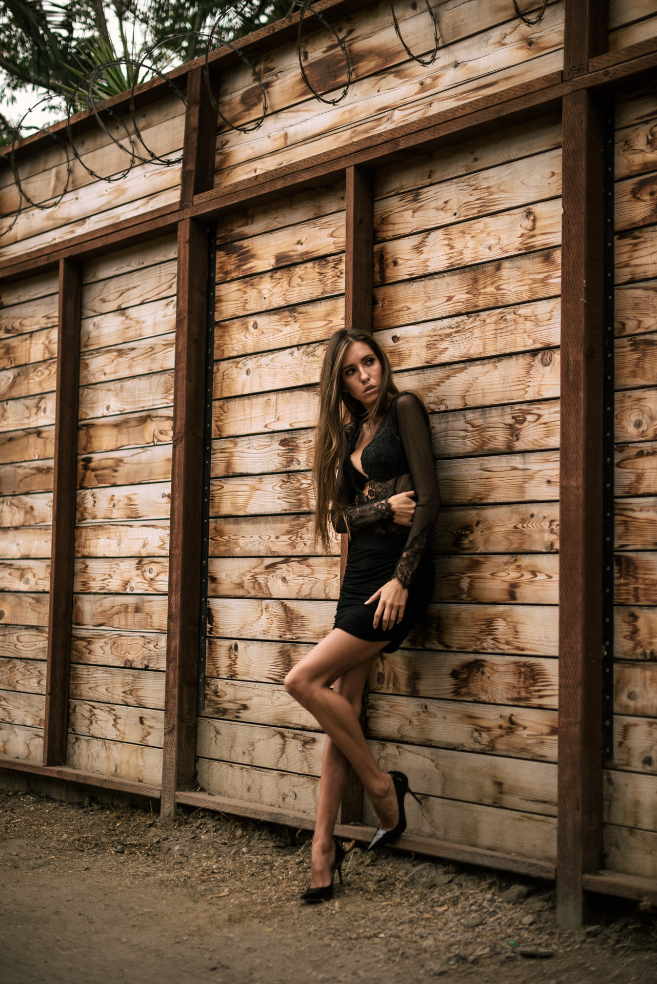 model poses in front of wooden wall with barbed wire at The Hungarion Brunette Lingerie as outerwear fashion photoshoot in Venice Beach California