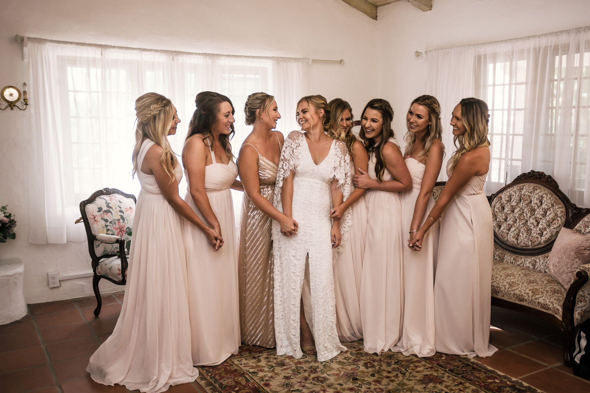 bride shares a good laugh with her bridesmaids while they pose for photos captured by photographer during romantic wedding at the historic Leo Carrillo Ranch in Carlsbad California