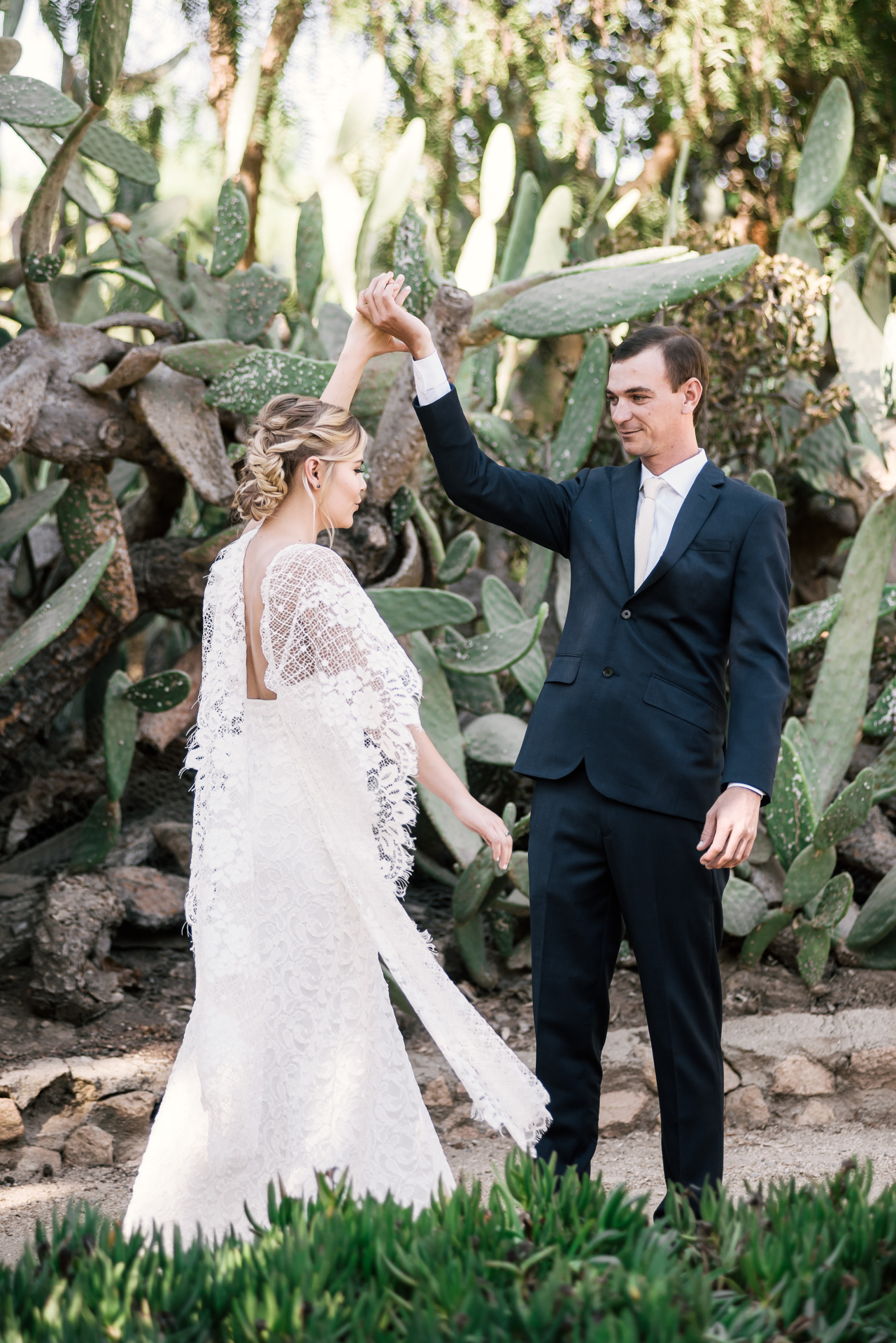 Groom gives his bride a twirl to showcase her dress captured by photographer during romantic wedding at the historic Leo Carrillo Ranch in Carlsbad California
