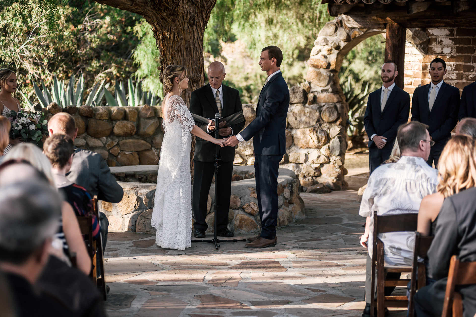 bride and groom prepare to say their vows captured by photographer during romantic wedding at the historic Leo Carrillo Ranch in Carlsbad California