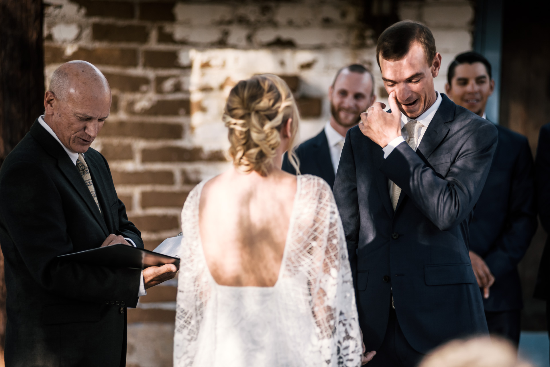 happy groom wipes tears of joy from his face captured by photographer during romantic wedding at the historic Leo Carrillo Ranch in Carlsbad California