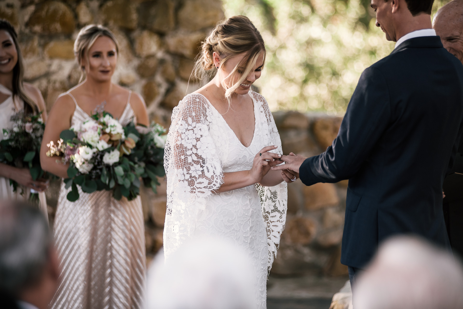 bride puts ring on grooms finger captured by photographer during romantic wedding at the historic Leo Carrillo Ranch in Carlsbad California