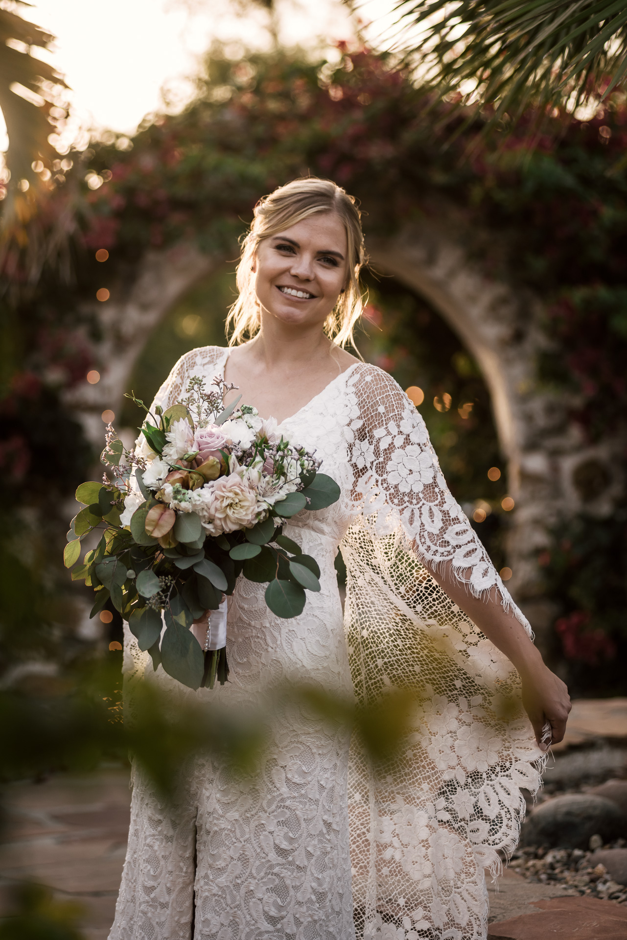 bride models her beautiful lace dress at sunset captured by photographer during romantic wedding at the historic Leo Carrillo Ranch in Carlsbad California