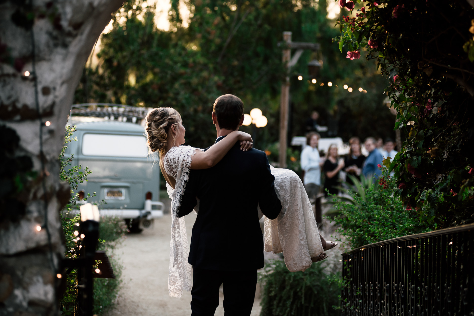 groom carries his bride to the reception captured by photographer during romantic wedding at the historic Leo Carrillo Ranch in Carlsbad California