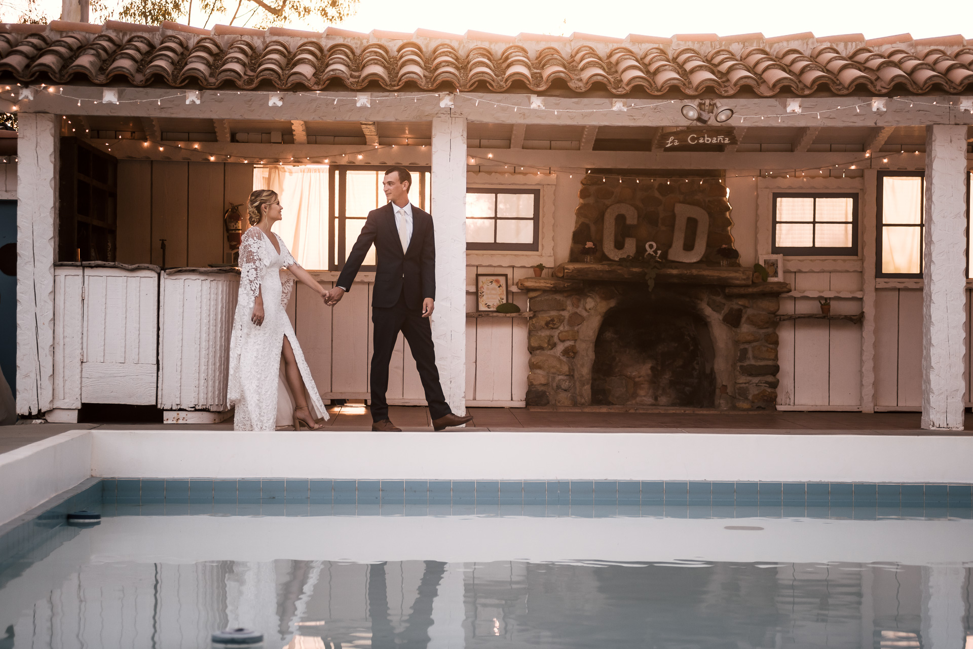 groom leads his bride past the pool captured by photographer during romantic wedding at the historic Leo Carrillo Ranch in Carlsbad California