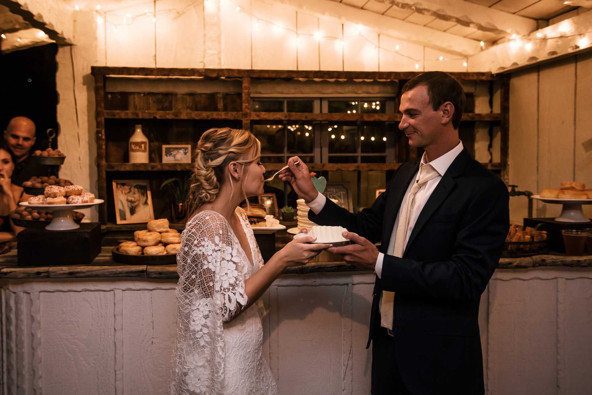 groom feeds his new wife cake captured by photographer during romantic wedding at the historic Leo Carrillo Ranch in Carlsbad California
