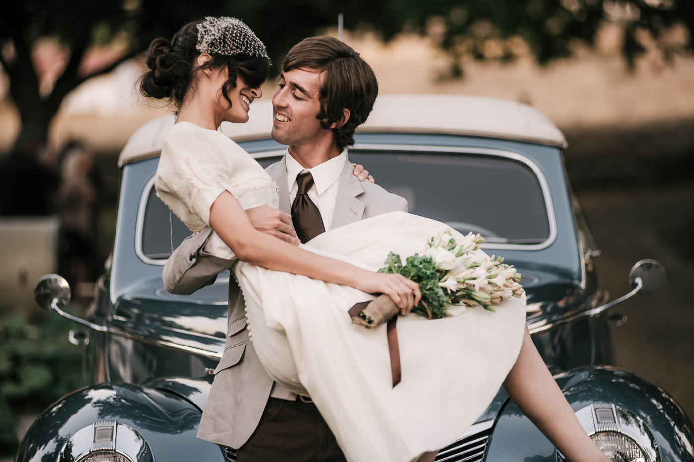 Bride and groom share a smile as he lifts her up in front of a classic car at their vintage wedding in the Temecula Wine Country