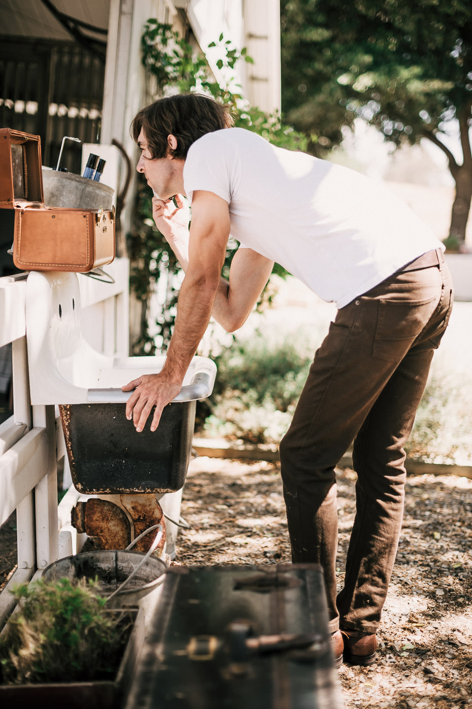 Groom gets a shaving kit from his bride as a gift and uses it at rustic washing station before his Temecula wine country wedding