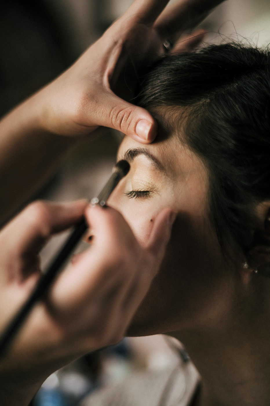 Makeup artist works on brides face before the big wedding in the temecula wine country