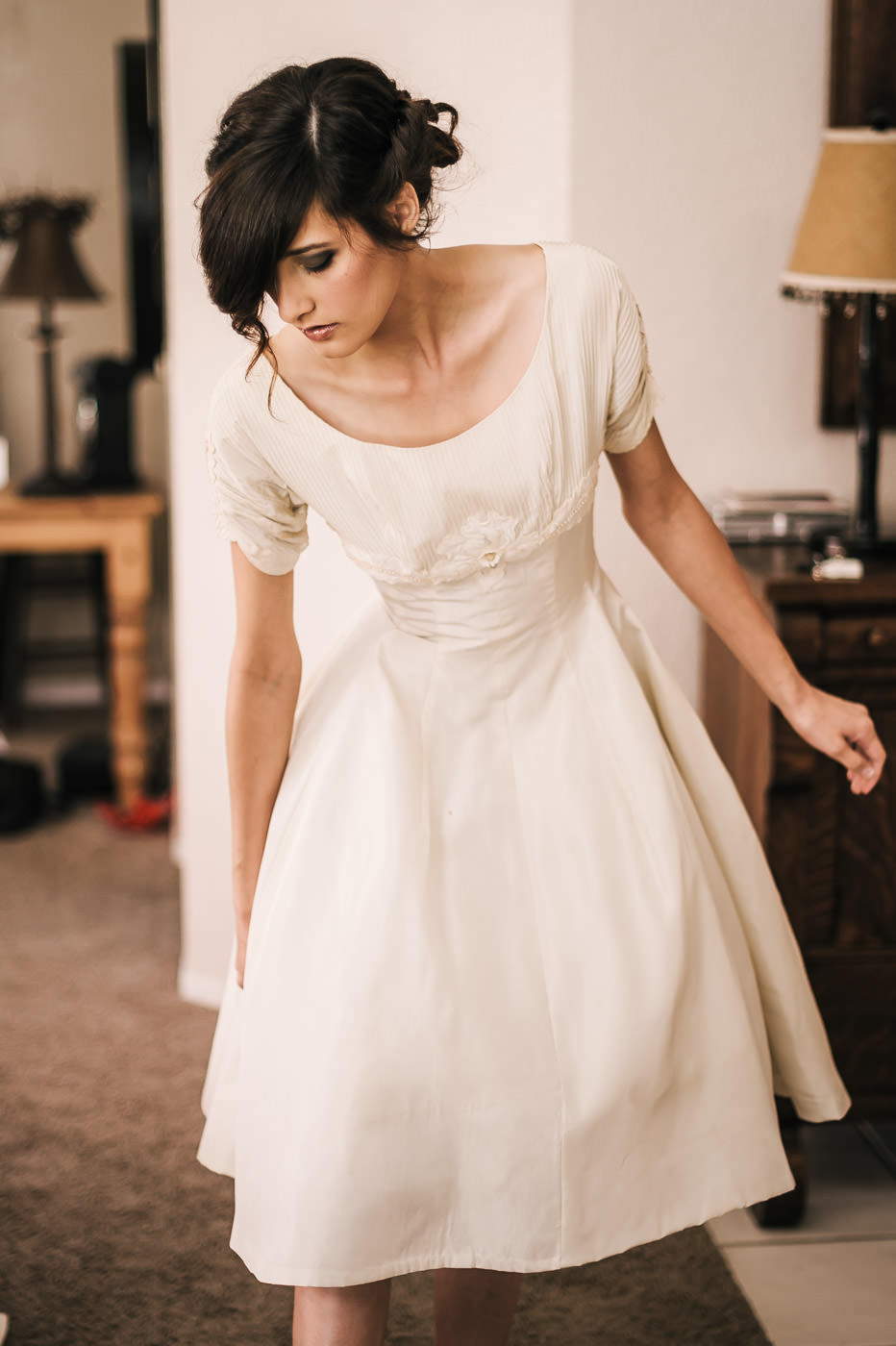 Bride puts on a vintage dress from her grandmother while getting ready for her romantic Temecula wine coutnry wedding