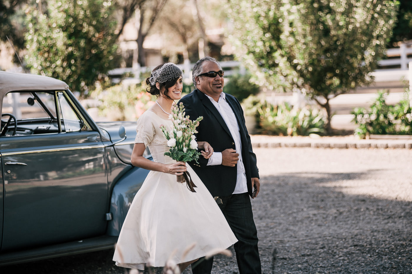 Father happily walks his daughter down the isle and she smiles as she sees the groom at their Temecula wine country wedding