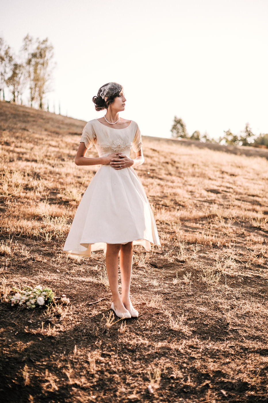 Classic vintage bride poses in the warm light of the setting sun in a simple field after her temecula wine country wedding