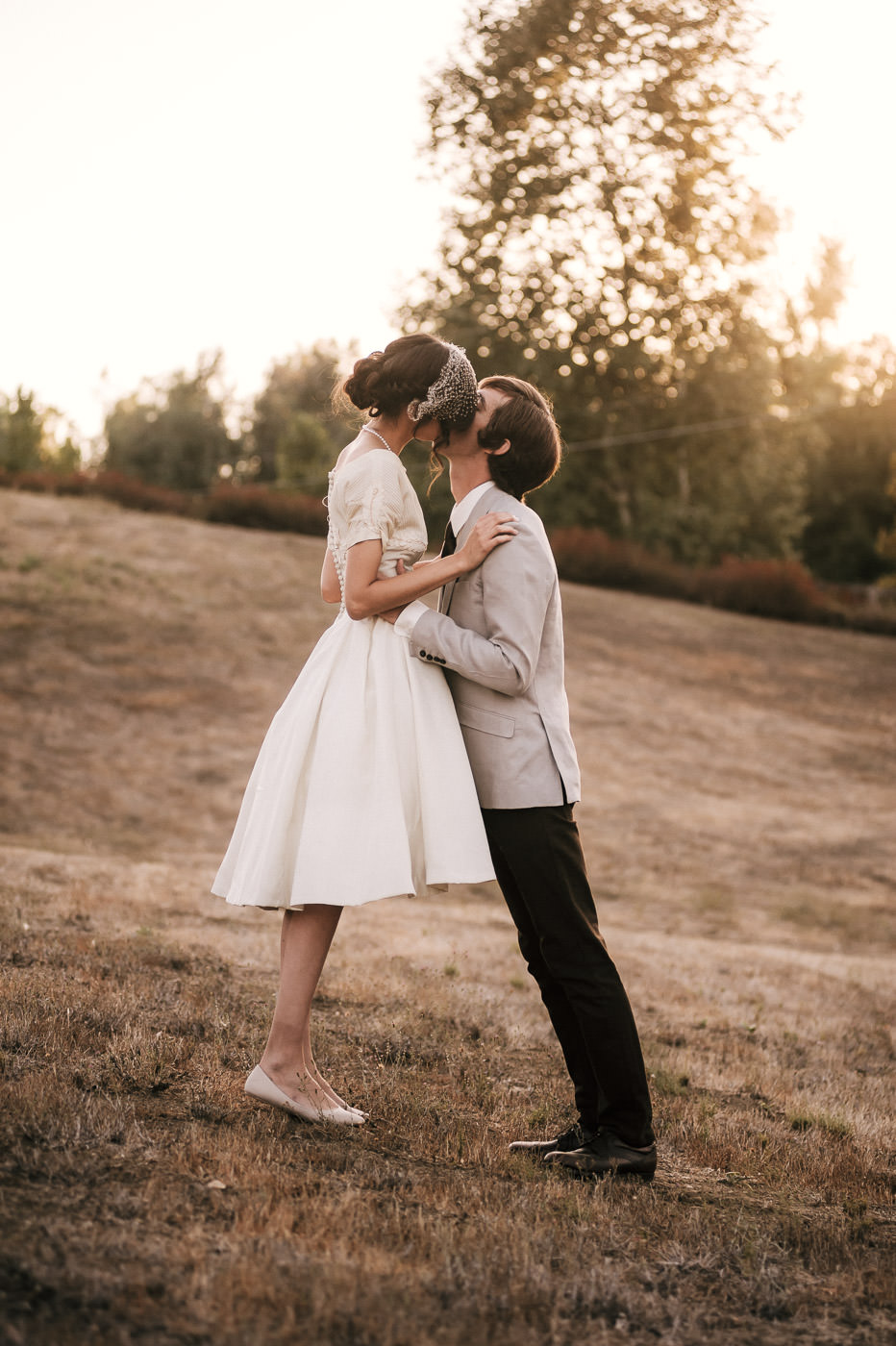 Cute couple with loads of vintage style kisses passionatly in a simple field as the sun sets on their Temecula wedding