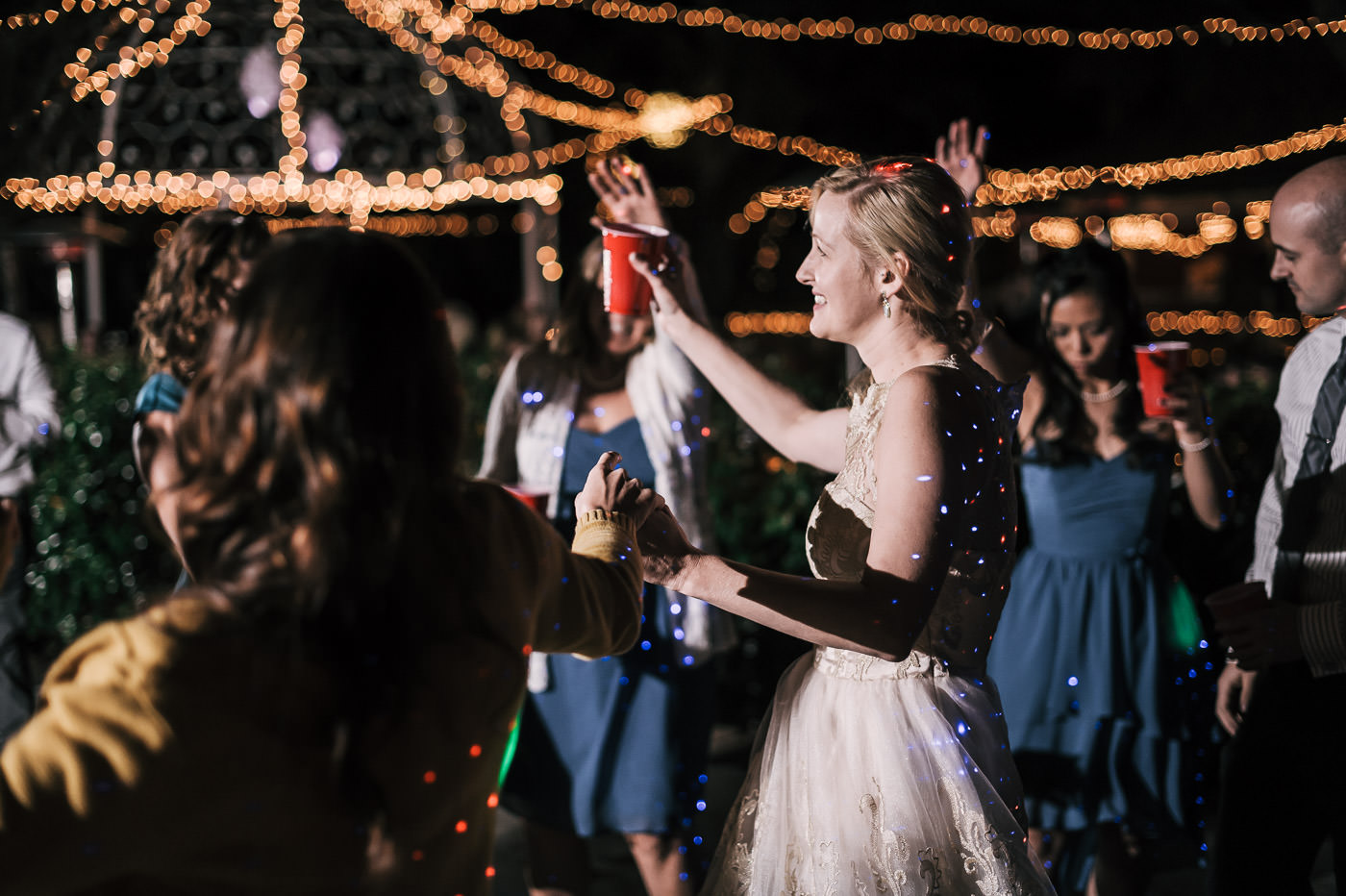 Bride celebrates with her guests under the twinkling lights of the whispering oaks terrace