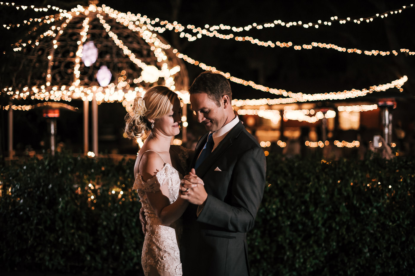 newly wed couple has their first dance under the twinkling lights of the beautiful wedding venue in temecula california