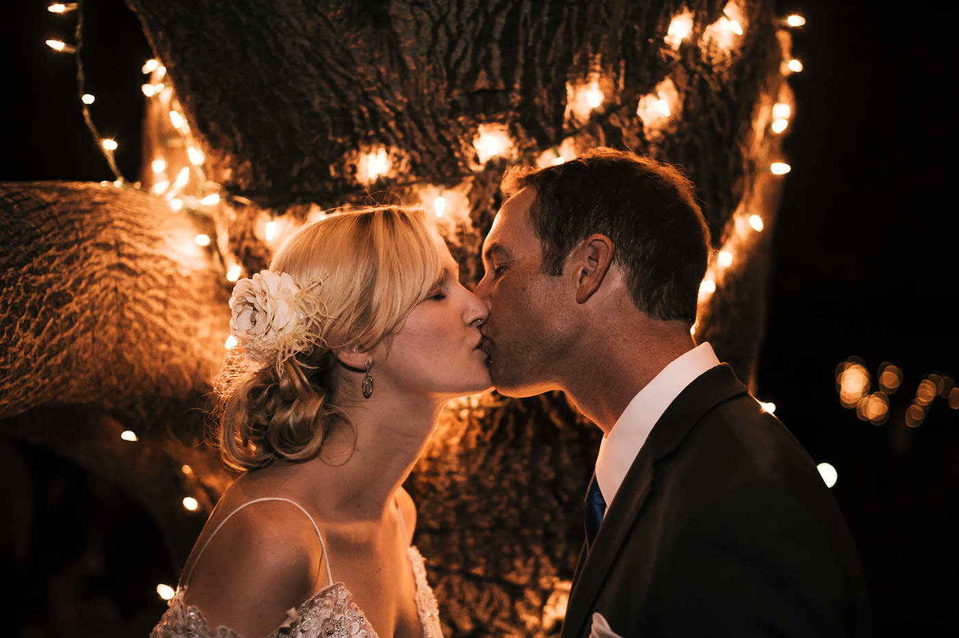romantic kiss under the oak tree lit by string lights at whispering oaks terrace