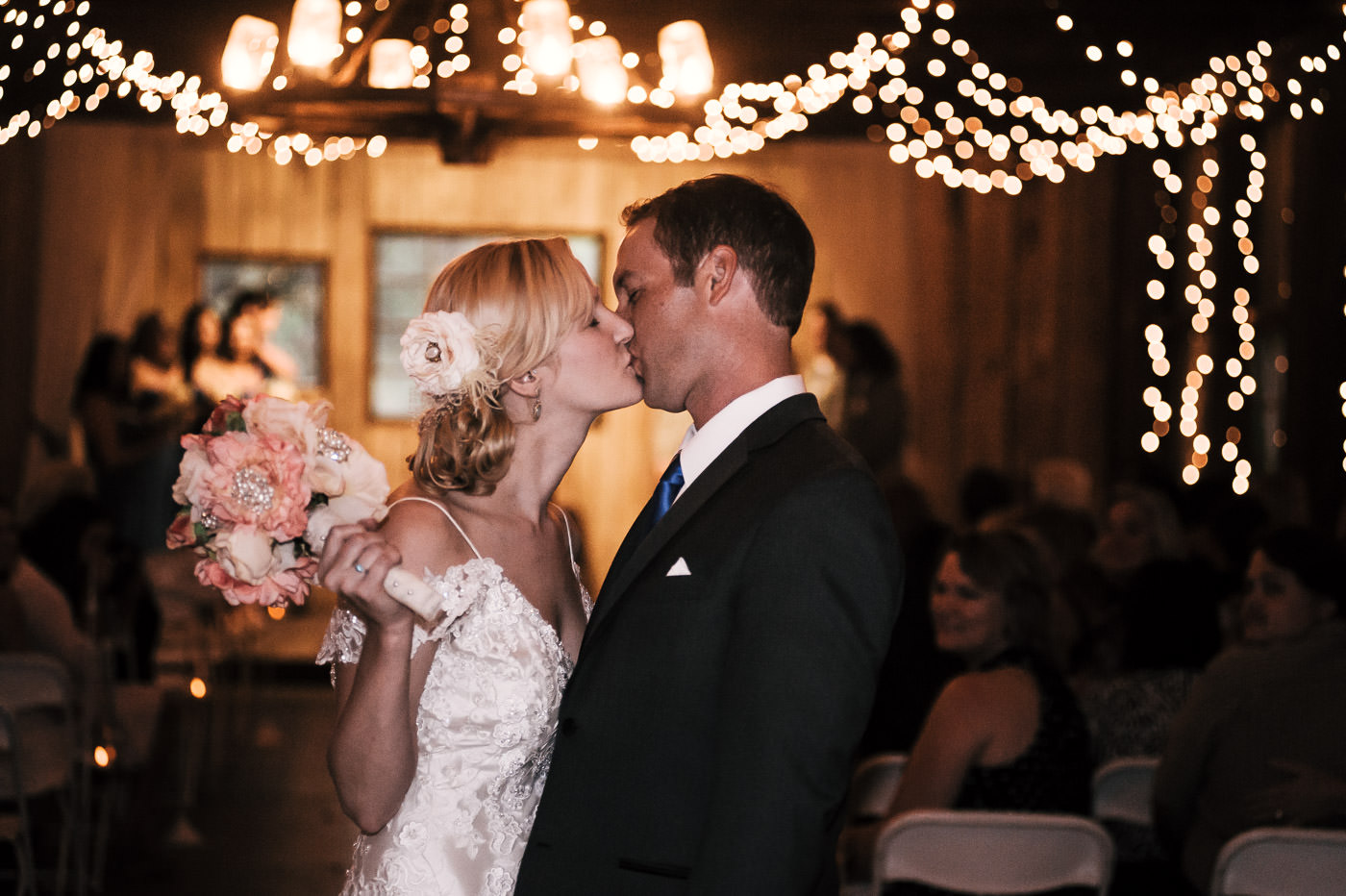 couple stops for one more kiss before they go down the aisle.