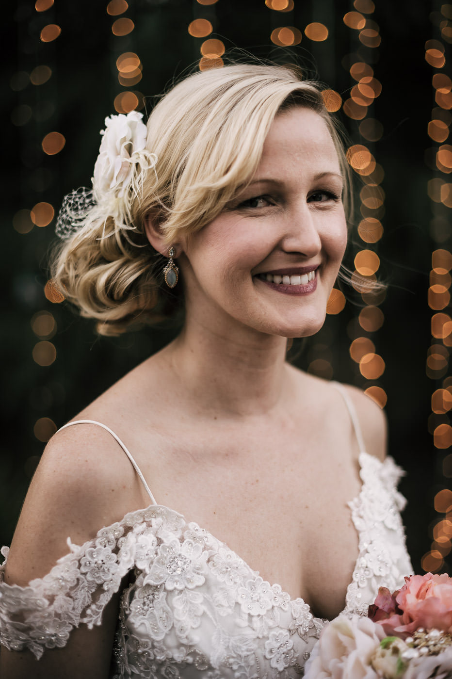 beautiful headshot of a vintage styled bride with gorgeous details and twinkling lights in the background