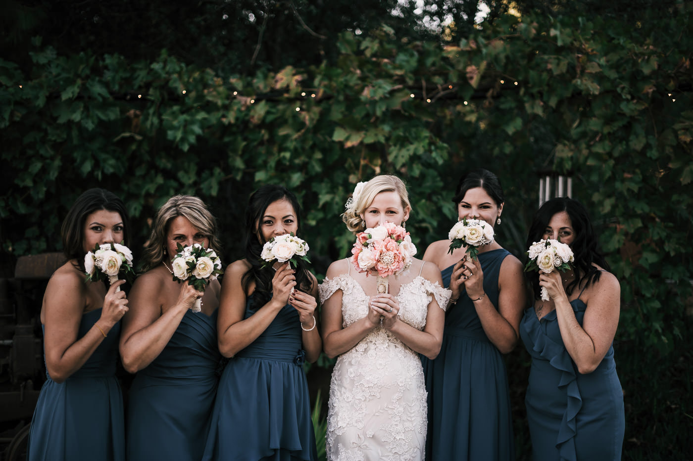 bride and her bridesmaids playfully hide behind their flower bouquets