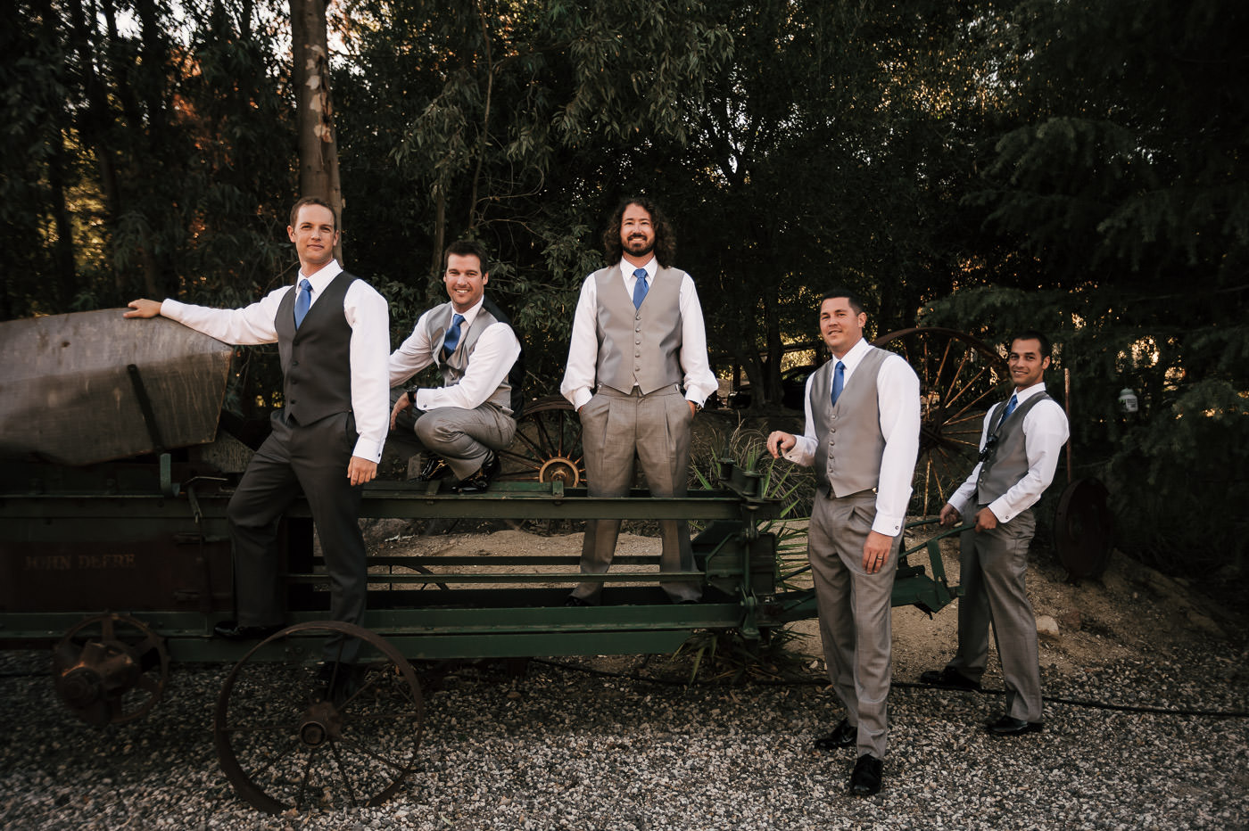 groom and his groomsmen poses on some old farm equipment