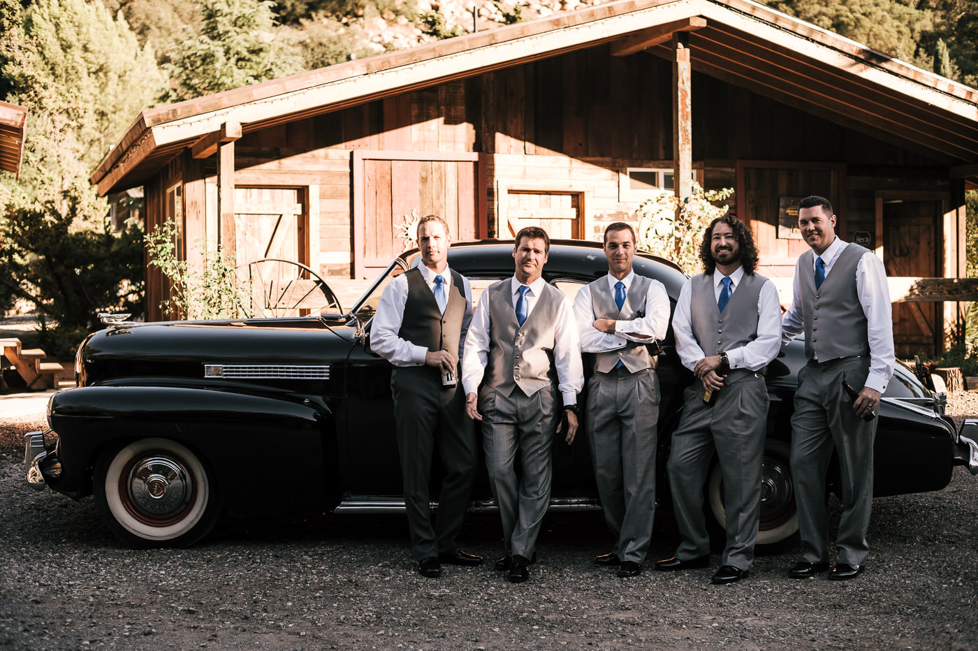 groom poses with his groommen next to a classic car at the rustic whispering oaks terrace in temecula california