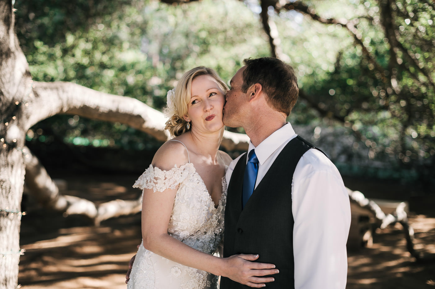 groom gives his bride a loving kiss on the cheek before they head off to the wedding ceremony at the whispering oaks terrace in temecula california