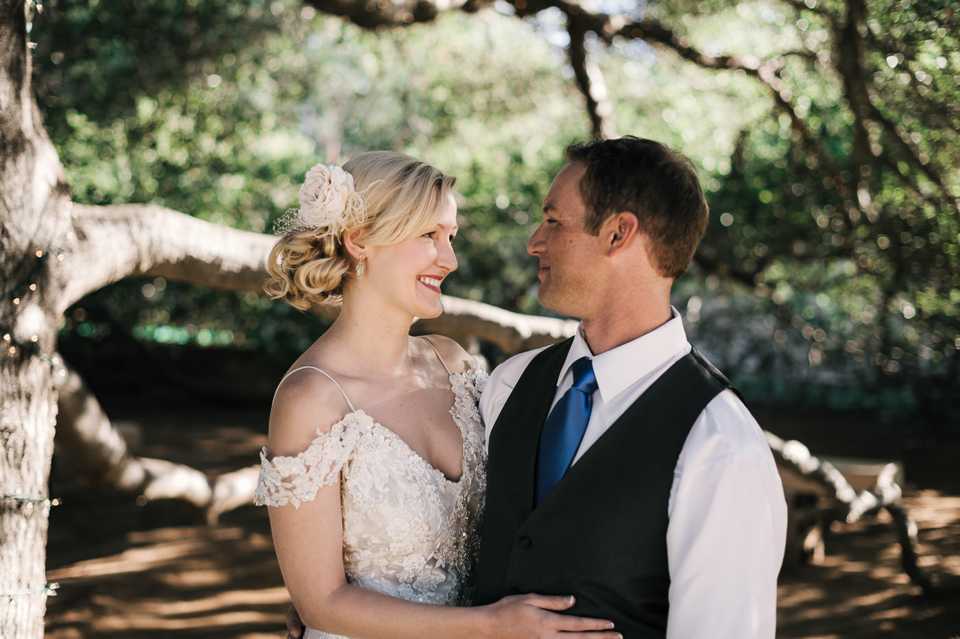 bride and groom enjoy the shade of an old oak tree as they smile at each other after an intimate first look