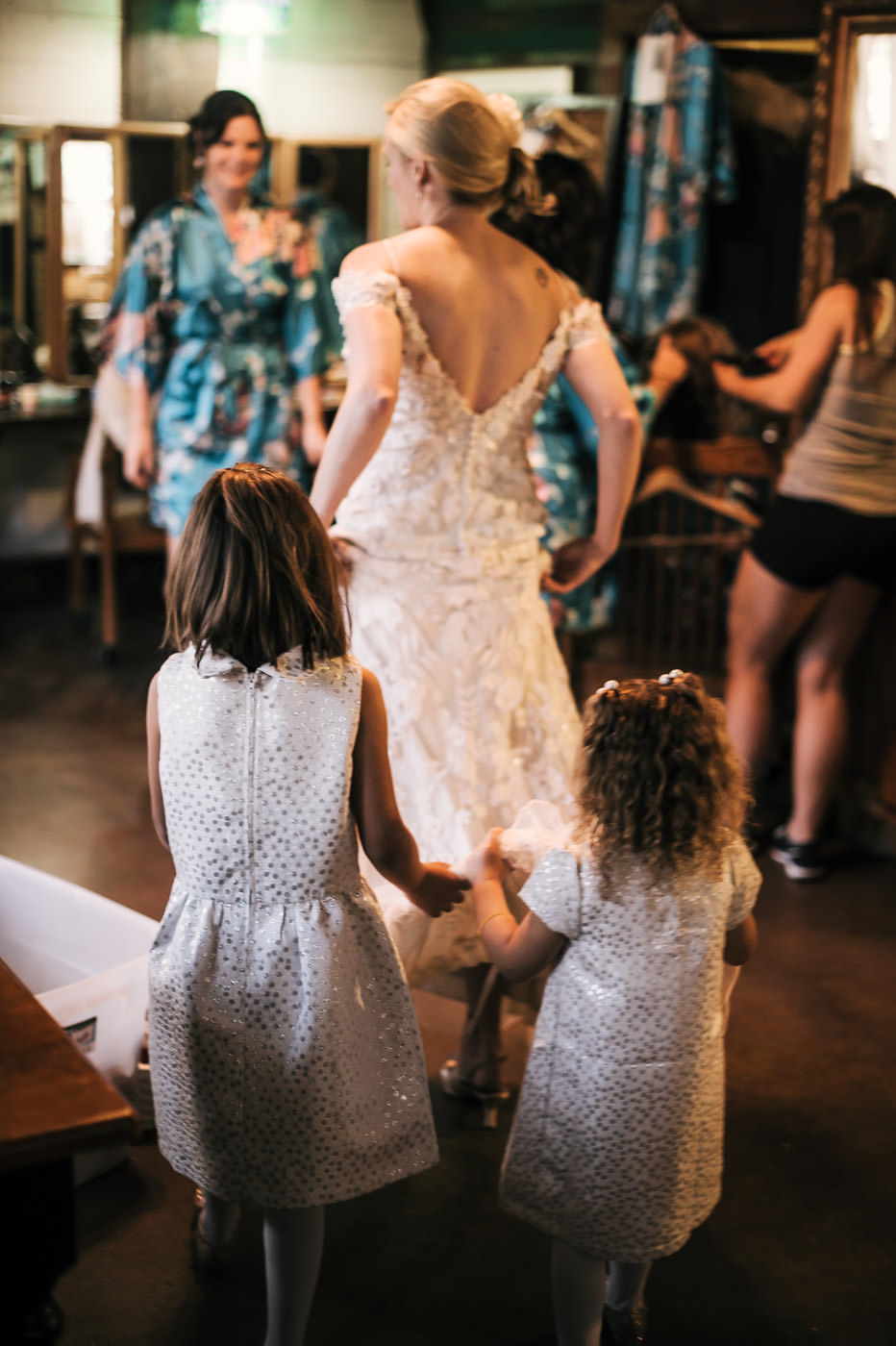 the brides little helpers assist her in moving around the bridal suite as she prepares for the first look
