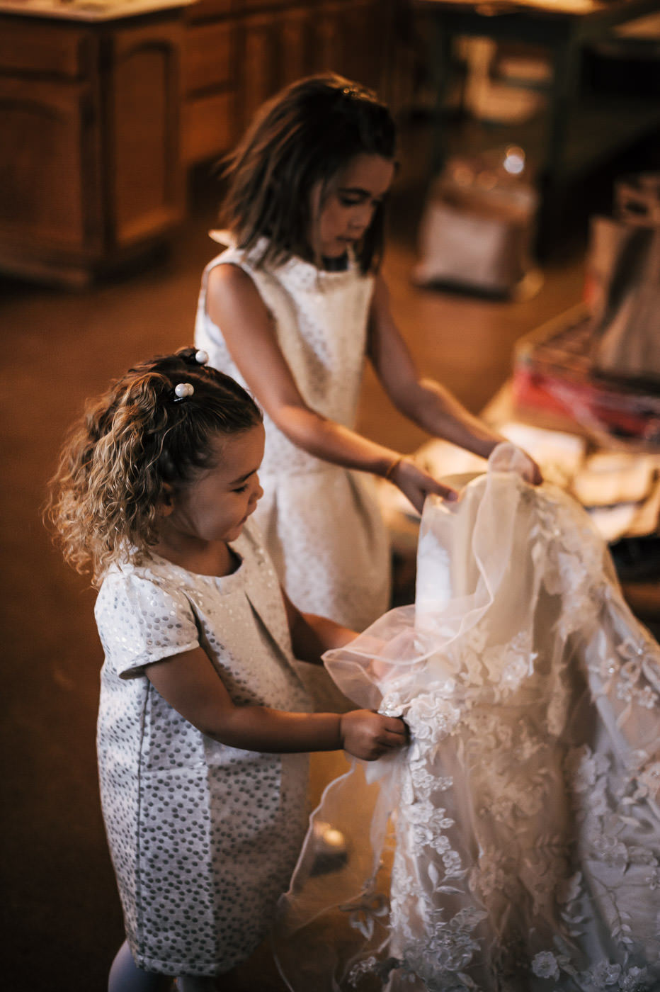 flower girls hold up the brides train while she get's ready for the wedding