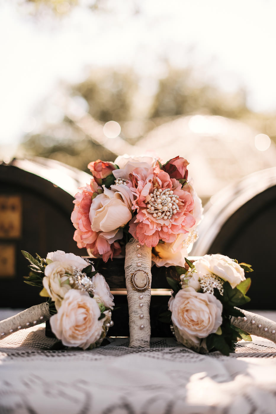 gorgeous pink and white bouquet with pearl and other vintage detials sits on a lace table cloth with the other bridesmaids flowers