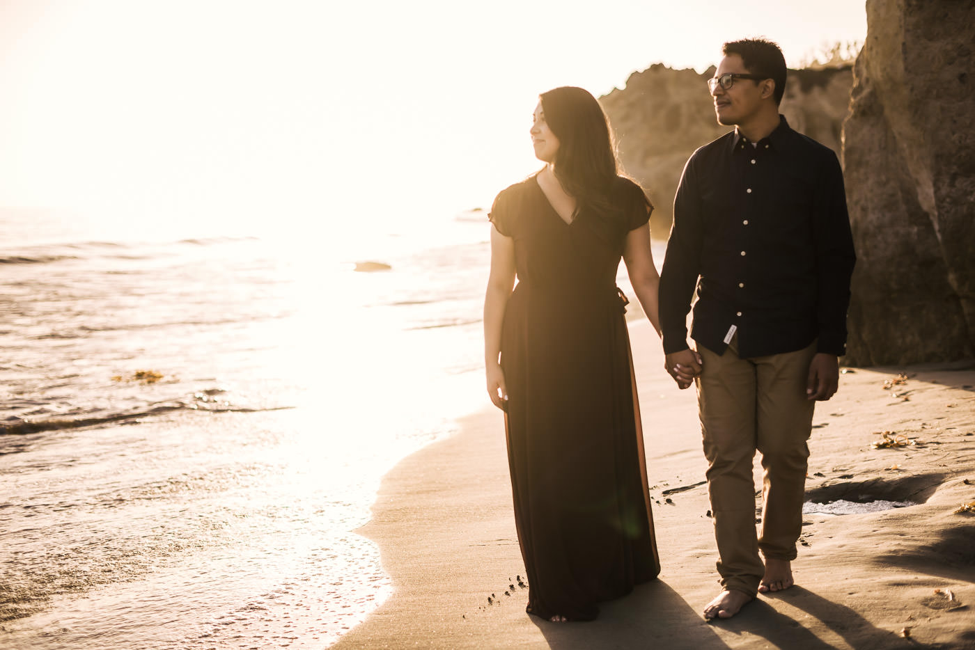 Couple walks hand in hand across El Matador State Beach as they stare off into the ocean and the setting sun in Malibu California
