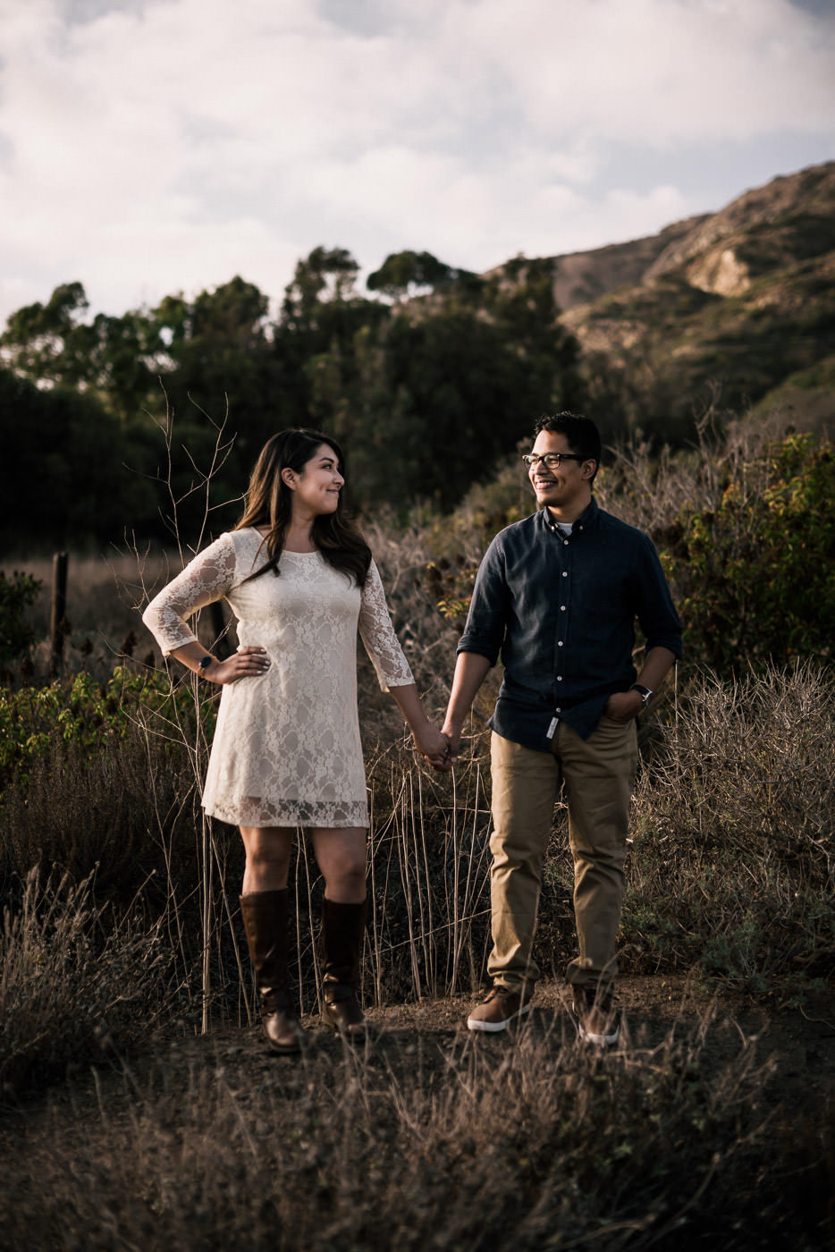 Couple stands side by side in the light of the setting sun on the cliffs of malibu for their engagement.