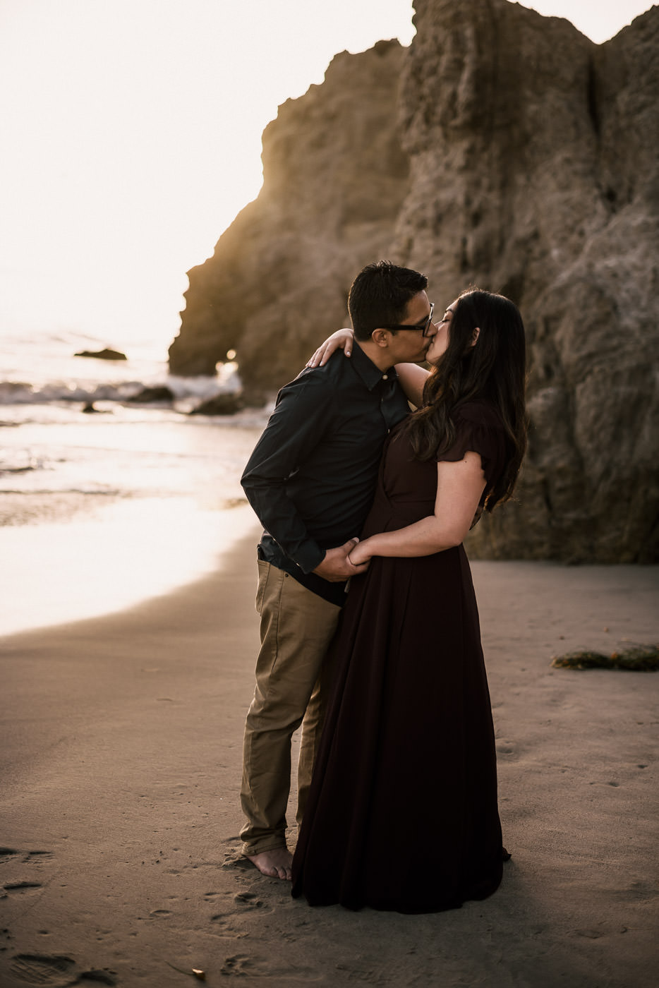Couple has a passionate kiss in the cool sand of El Matador state beach in Malibu at sunset.