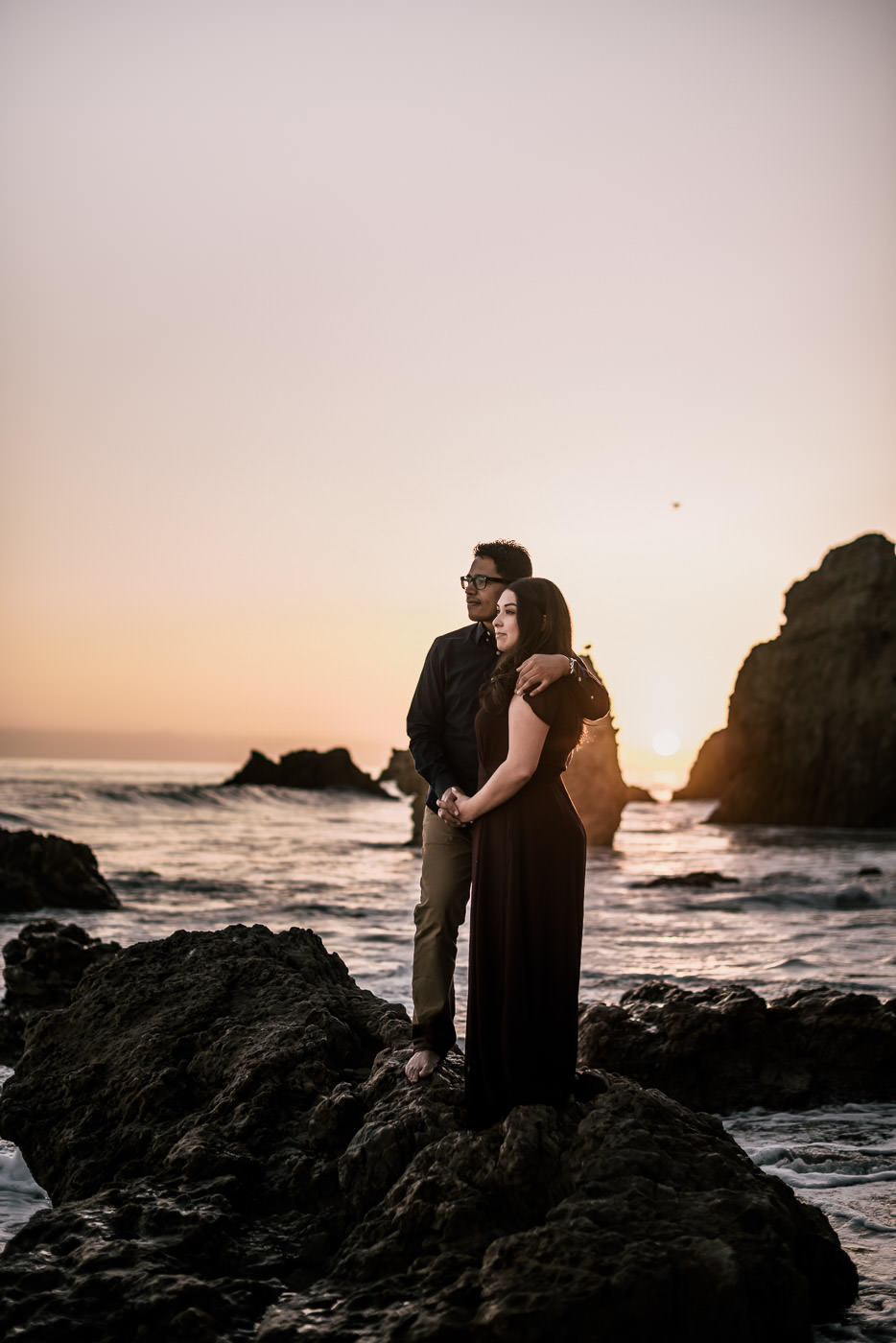 The soft golden light of sunset highlites this loving couple as they stand fast on the rocks with the sea all around them. A Romantic portrait from their El Matador Beach Engagement session in Malibu California.