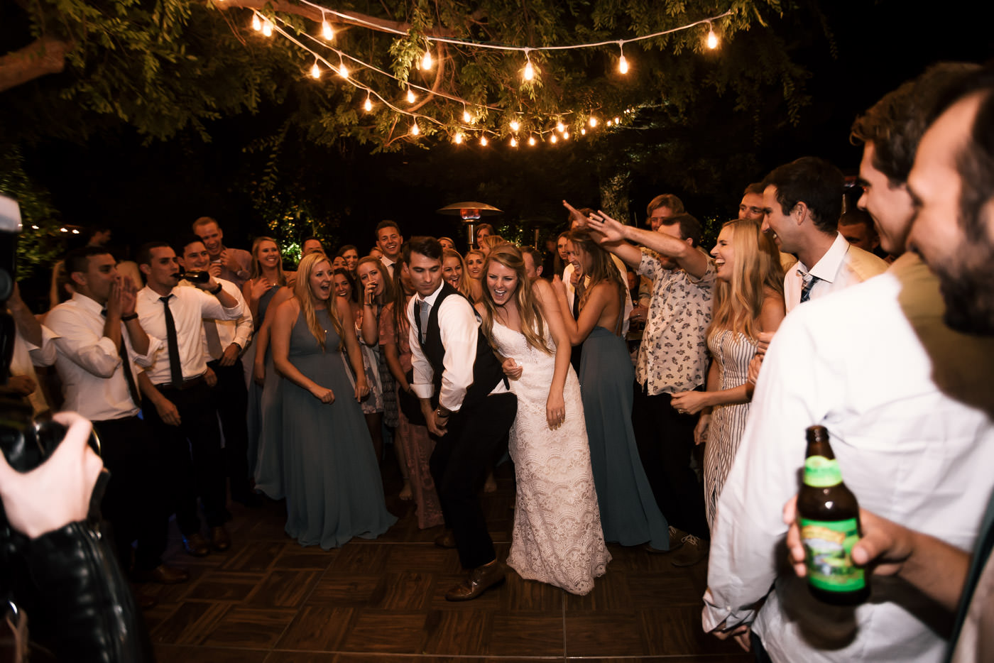 Newly married couples tears it up on the dance floor with their guests after their wedding.