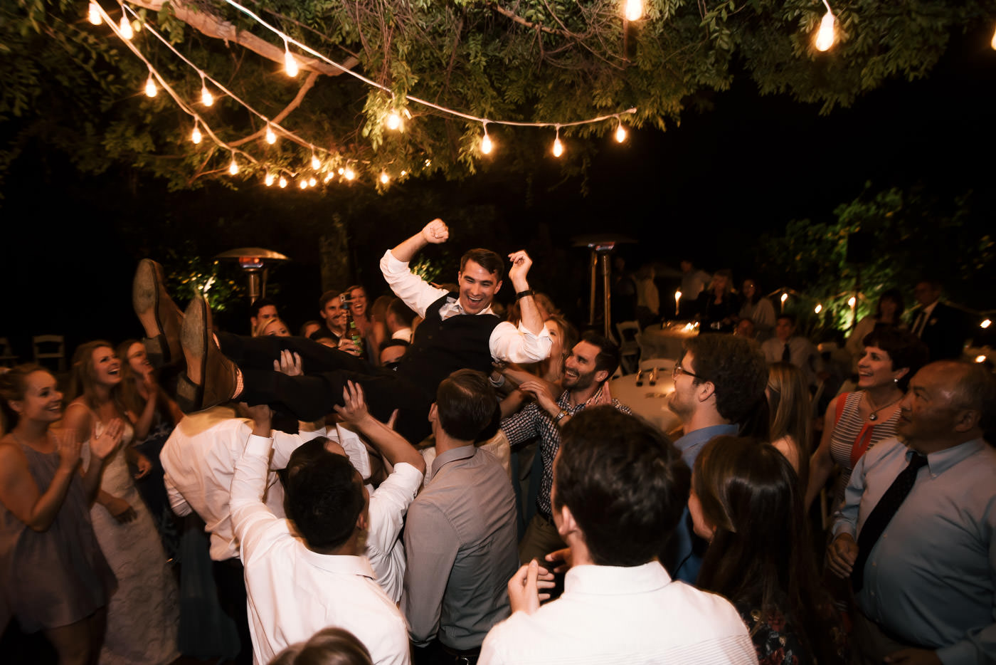 Wedding guests lift the groom into the air and carry him across the dance floor in Temecula California