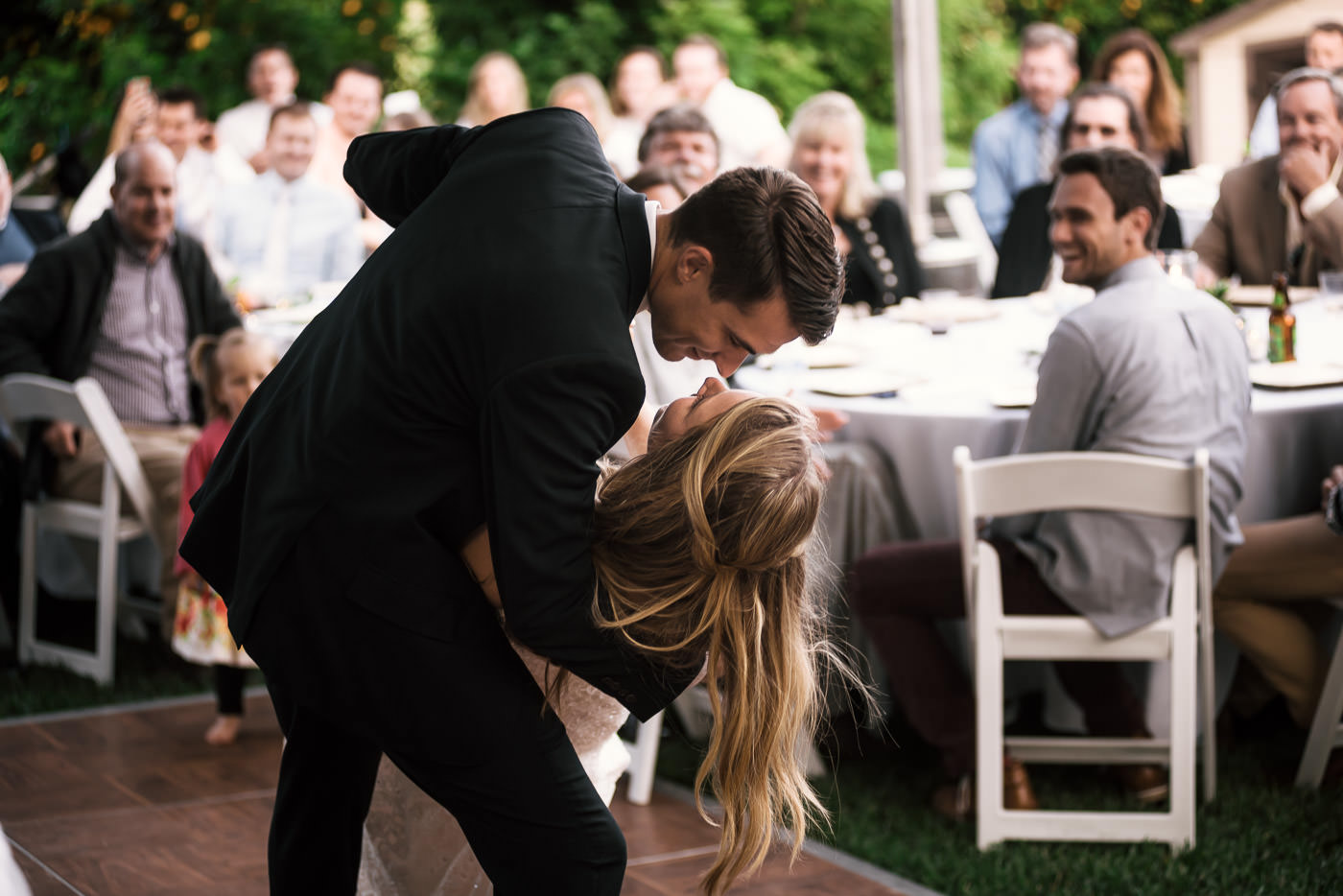 Couple shares in their first dance together and gets lost in romance as the groom dips his new bride.