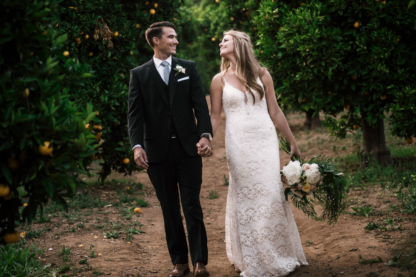 Happy couple is all smiles as they triumphantly walk through the trees of the orchard on the way to their wedding reception in Temecula California