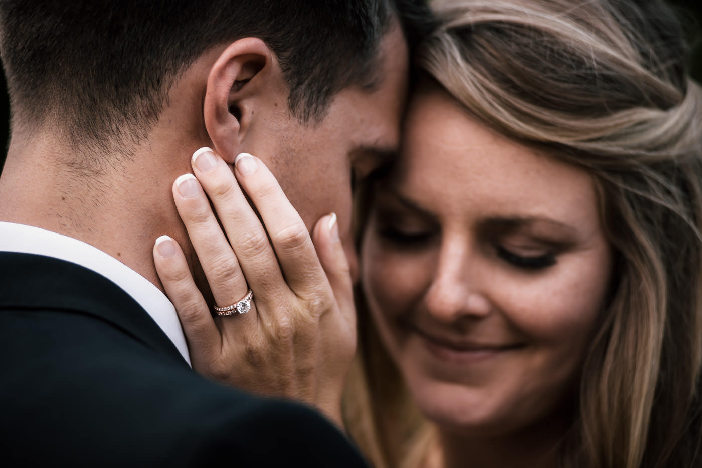 Bride places her hand tenderly on her husbands face and shows off her rings as the couple snuggles in close.