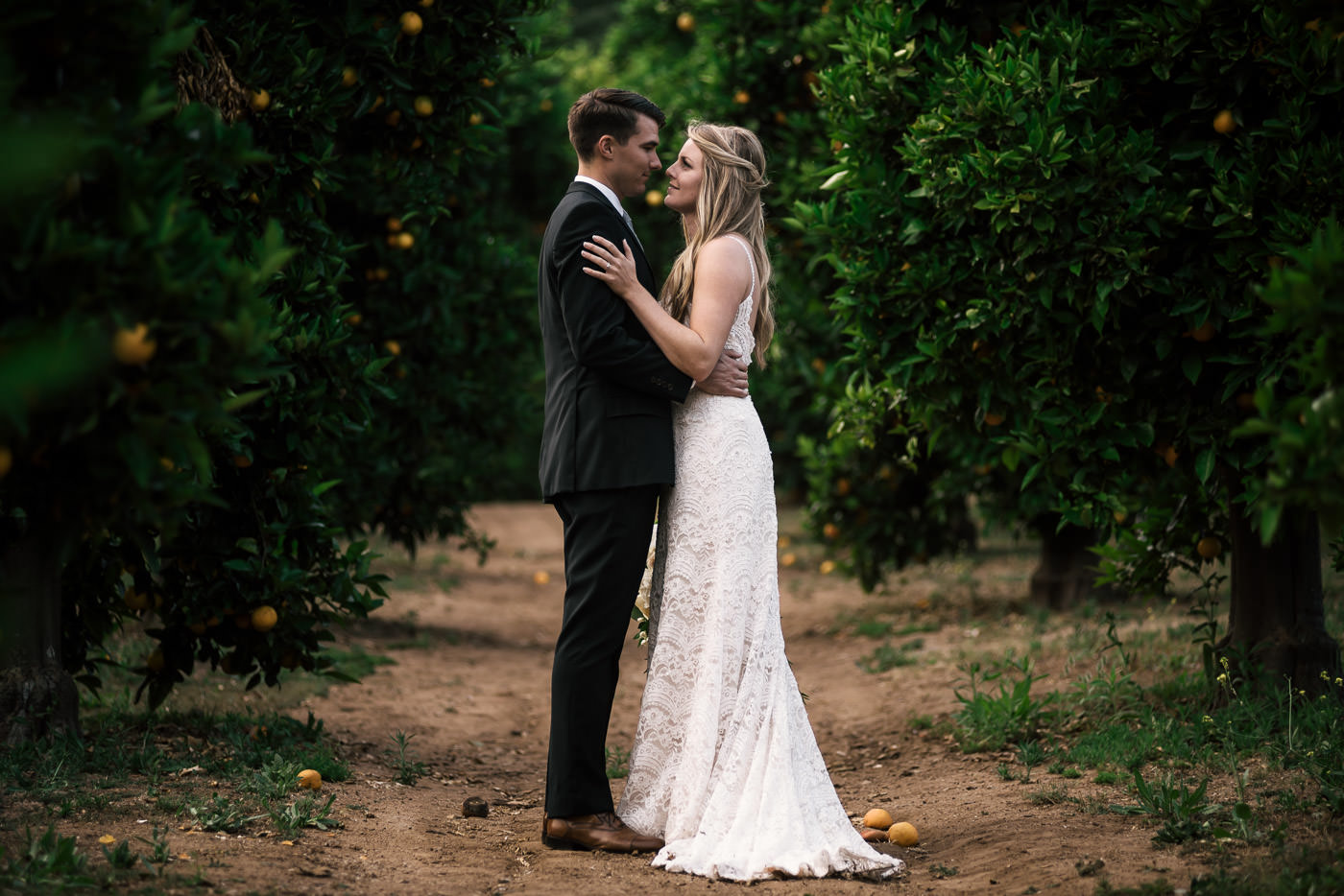 Couple stops for a little romance in the orchards of Temecula California. This romantic moment was captured by their wedding photographer.