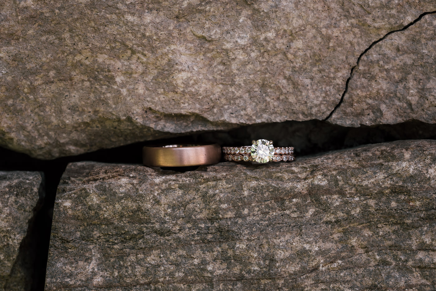 Wedding rings sit beside eachother in the narrow gap between stones on a rock wall.