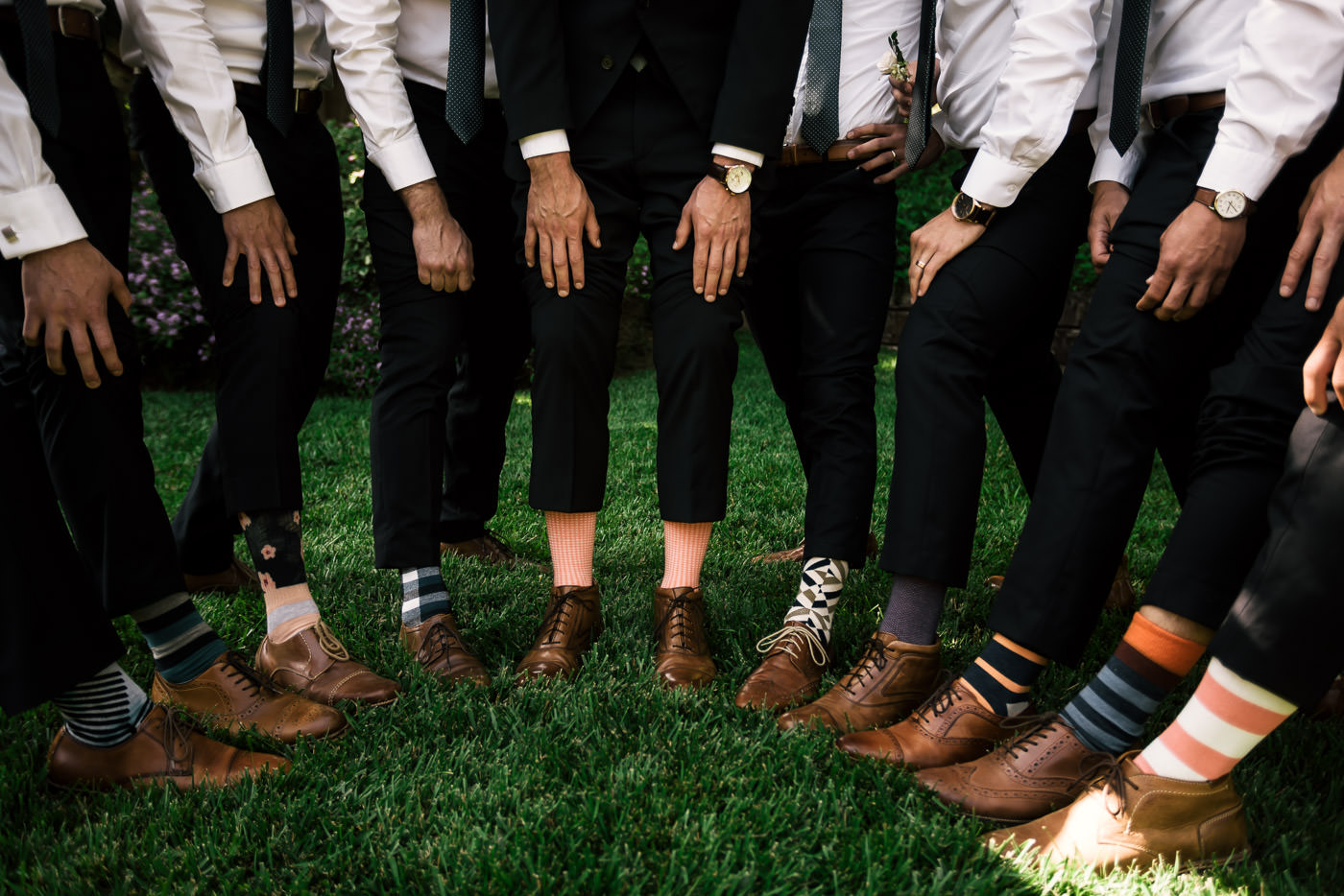 Groom and his groomsmen show off their crazy socks and stylish shows captured by a Temecula wedding photographer.
