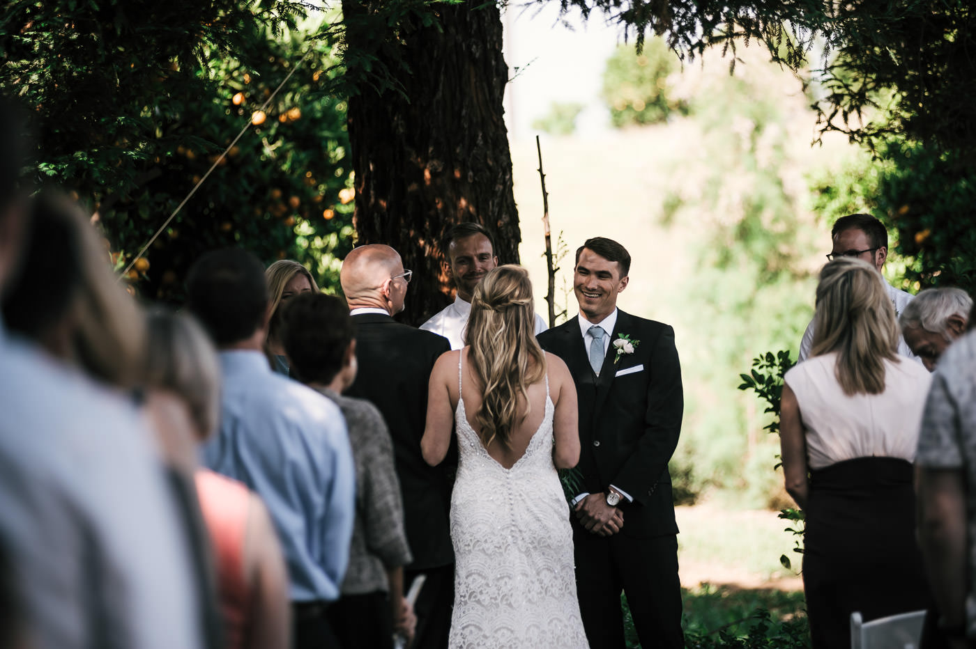 Temecula wedding photographer captures this happy groom turn to all smiles as he sees his bride coming down the aisle at their ceremony.