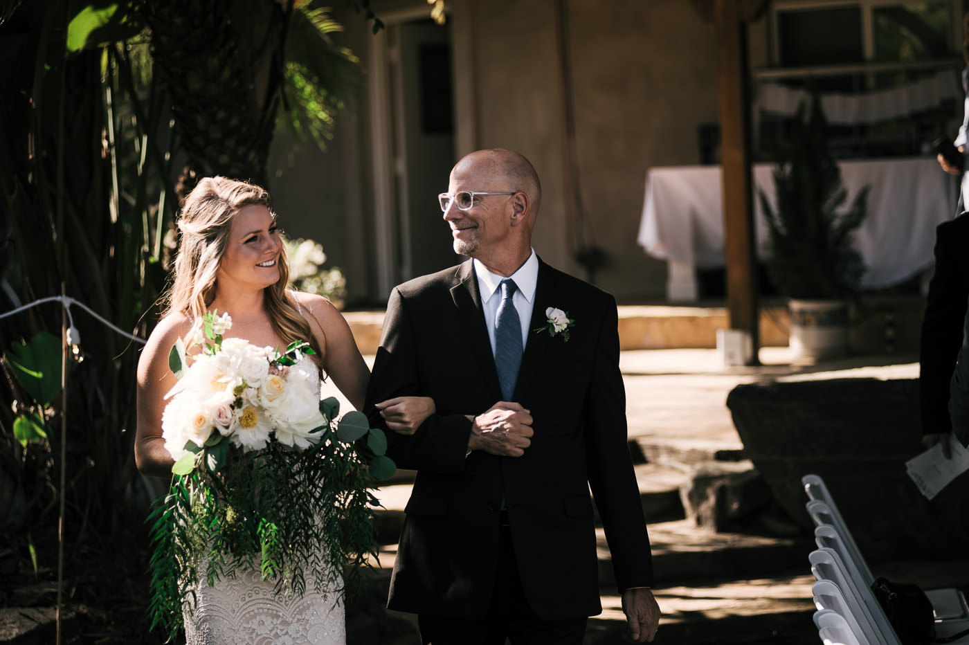 Father walks the bride down the aisle with smiles all around. A touching moment captured by their Temecula wedding Photographer
