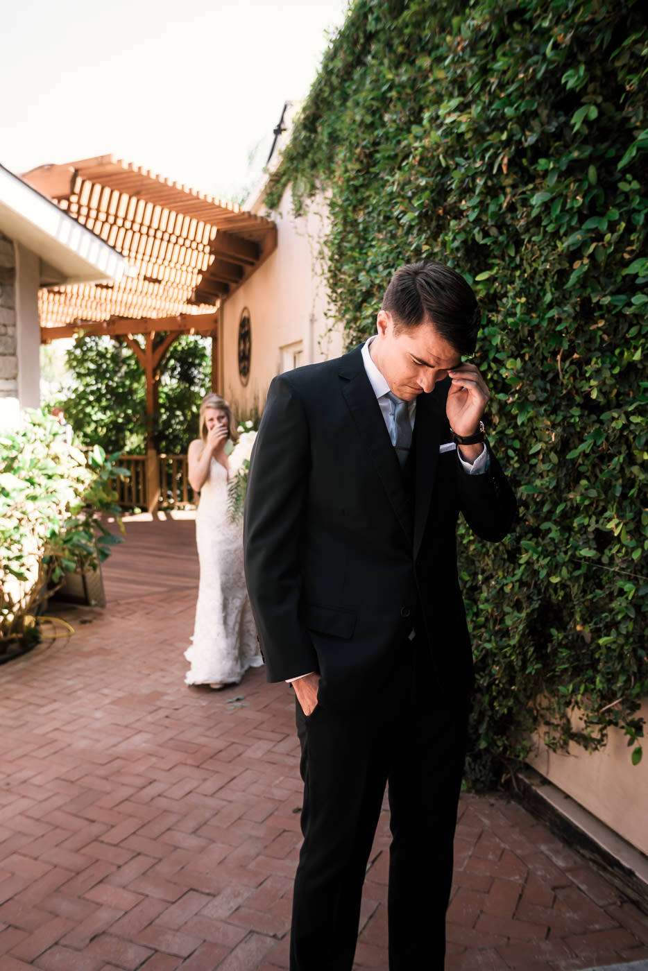 Groom sheds tears of joy as he hears his bride coming. He anxiously anticipates seeing her for the first time at their Temecula wedding.
