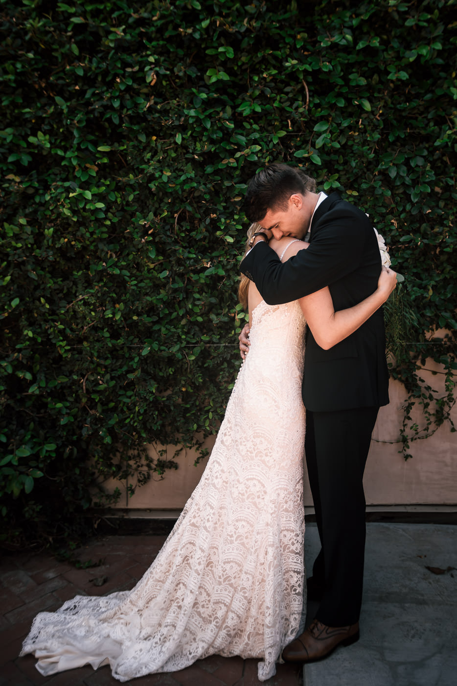 these two soon to be newlyweds hugged each other tightly as their joy overflowed after their first look in front of an ivy wall before the wedding in temecula