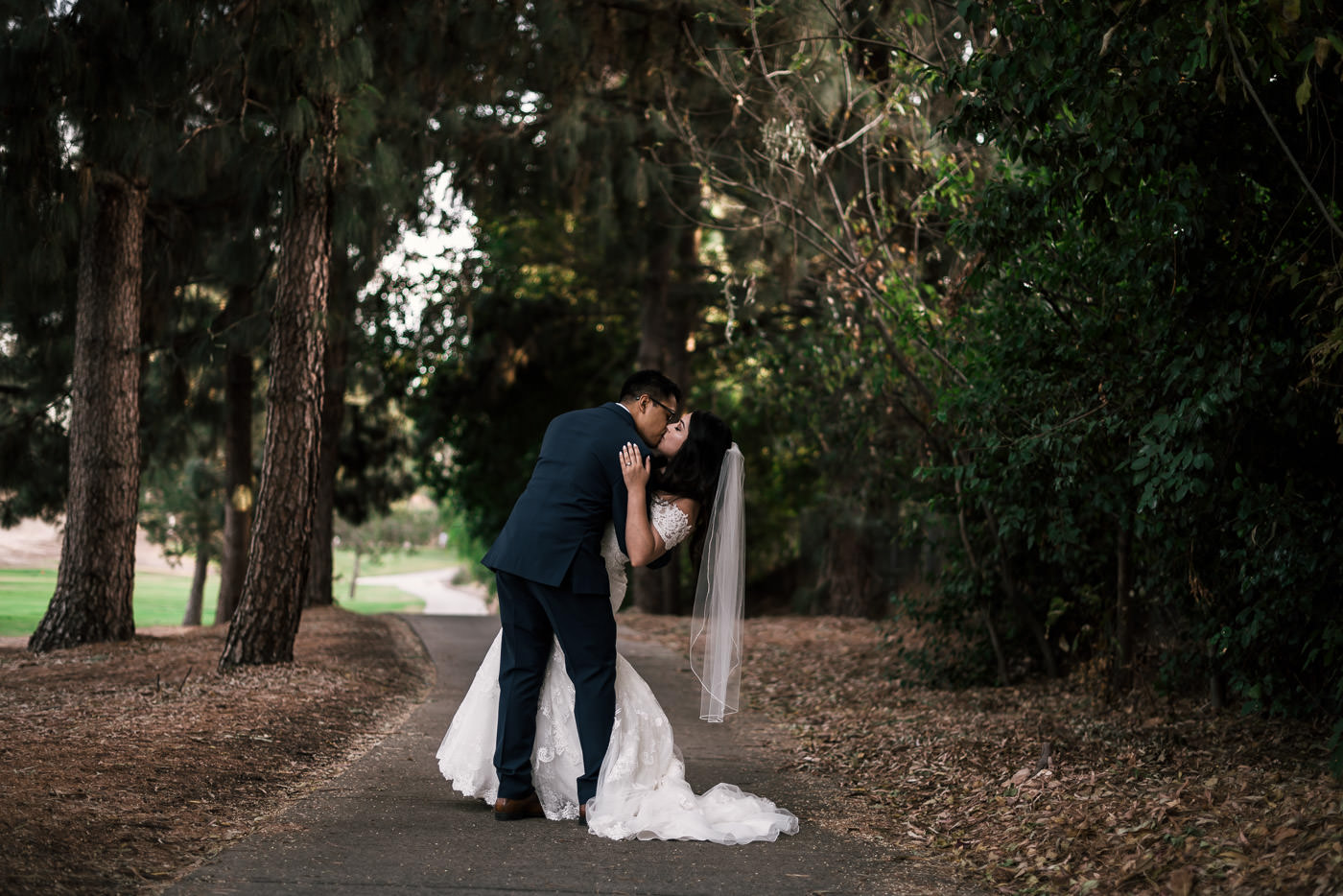 groom romantically kisses bride as he dips her after their wedding at the knollwood country club in granada hills
