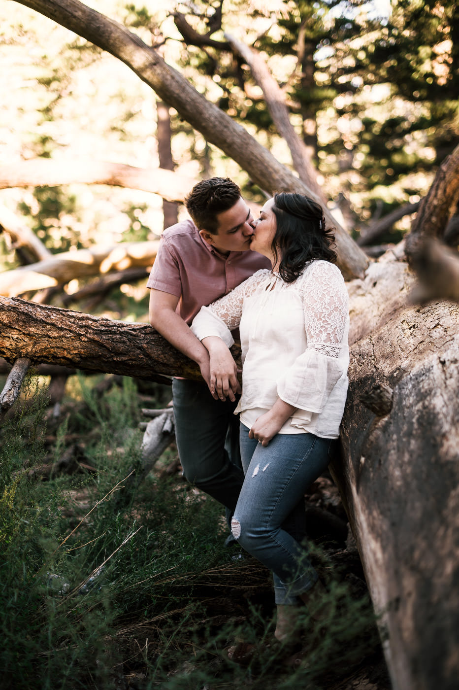 Couple has a romantic kiss next to a fallen tree in the woods of Mt San Jacinto.