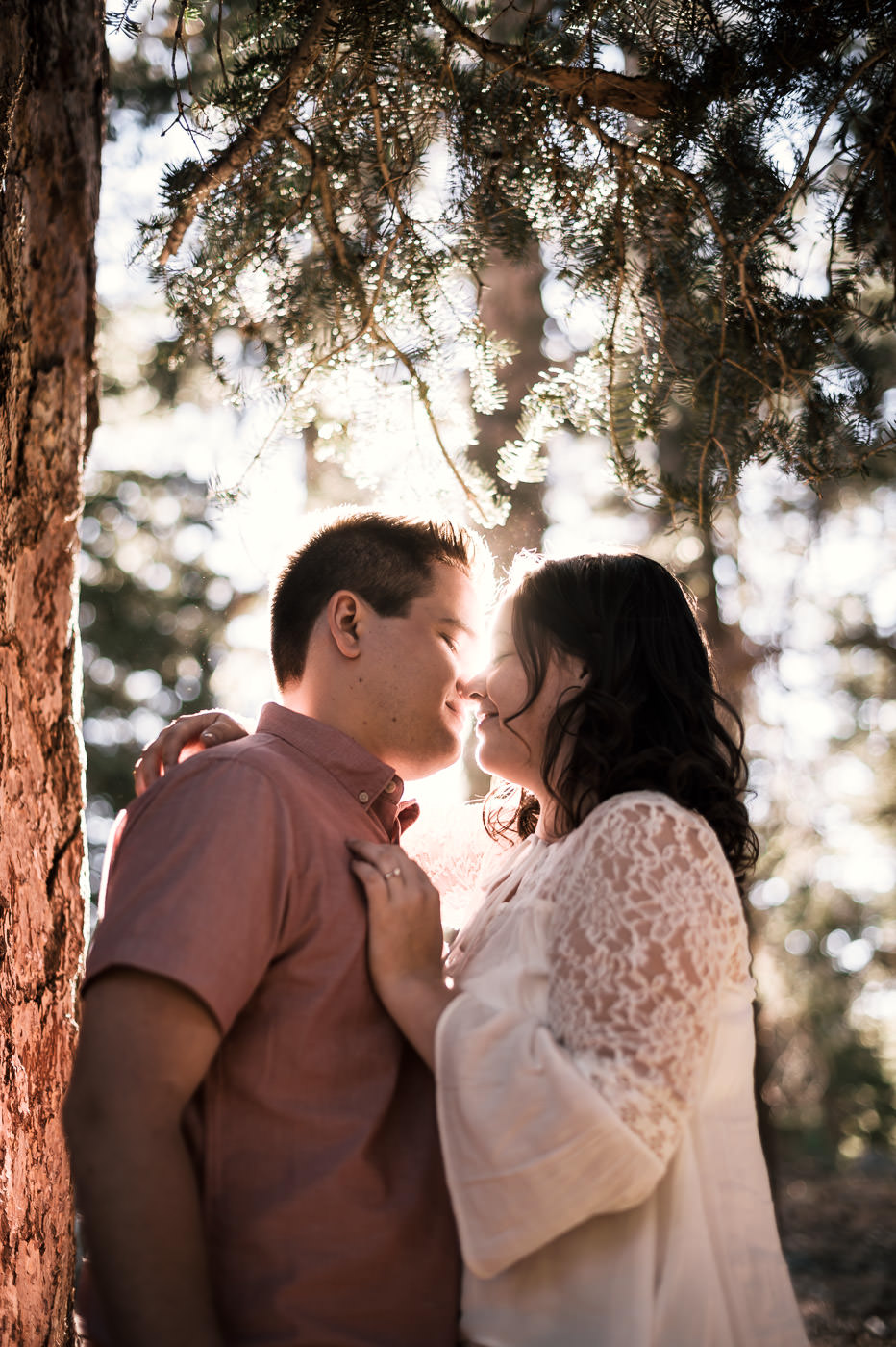 The bright light of sunset filters through the trees behind this engaged couple.
